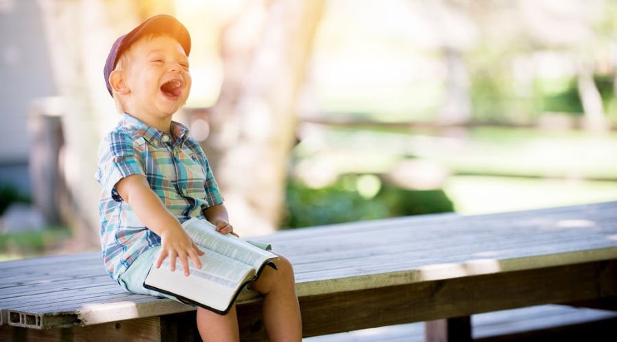 Small child laughing on a bench in a park